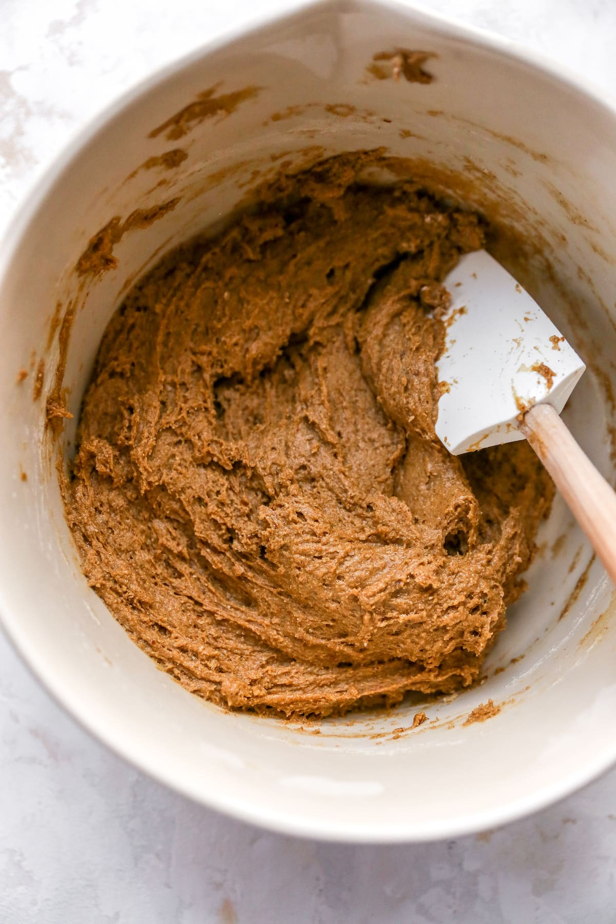 Mixing bowl of coffee cake batter with a spatula.