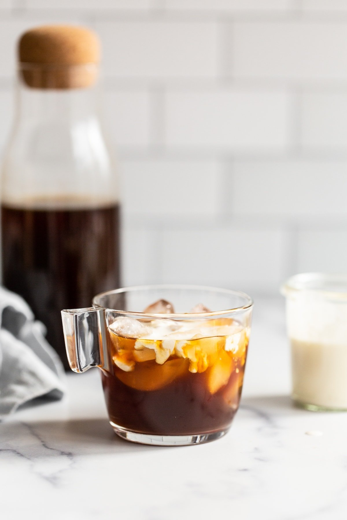 Glass jar with cold brew and cream mixing into the coffee.
