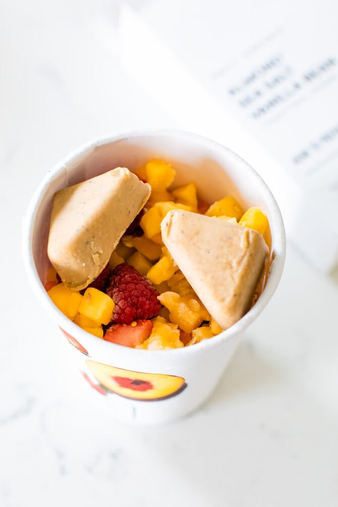 Daily Harvest peach raspberry smoothie cup with two nut mylk wedges on top.