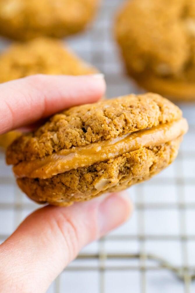 Hand holding a peanut butter sandwich cookie.