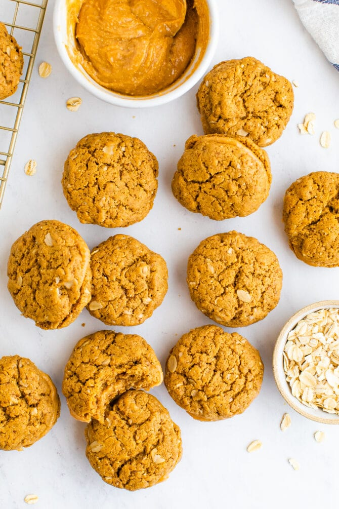 Do si do cookies on a table next to a bowl of peanut butter and oats.