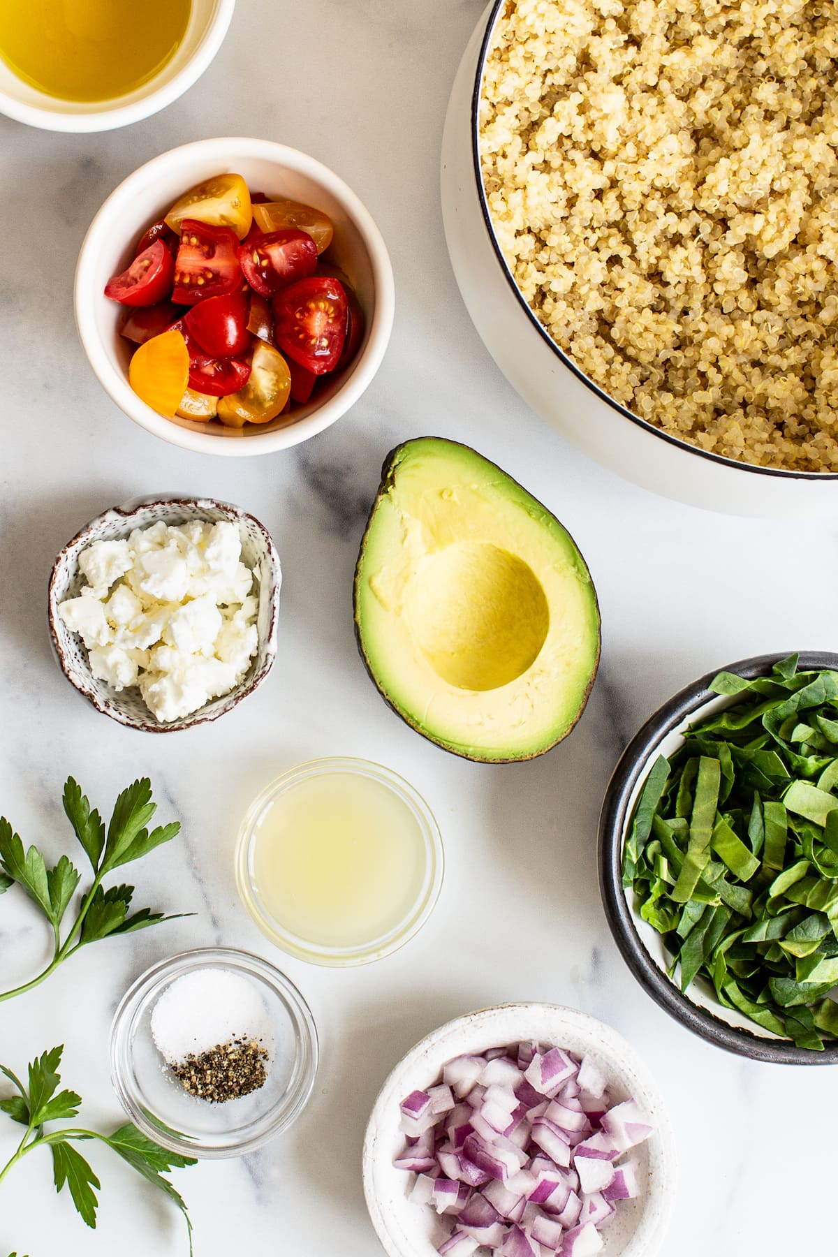 Quinoa, tomatoes, avocado, feta, spinach, lemon juice, spices and red onion measured out in bowls.