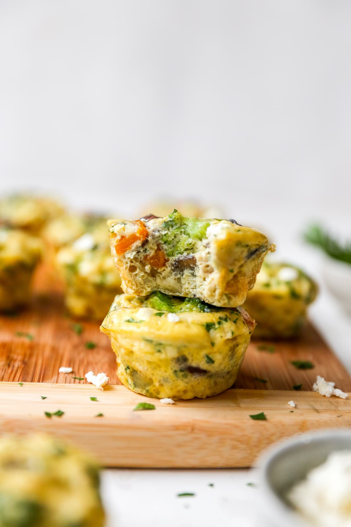 Two stacked egg muffins with veggies. The top egg cup has a bite taken out of it.