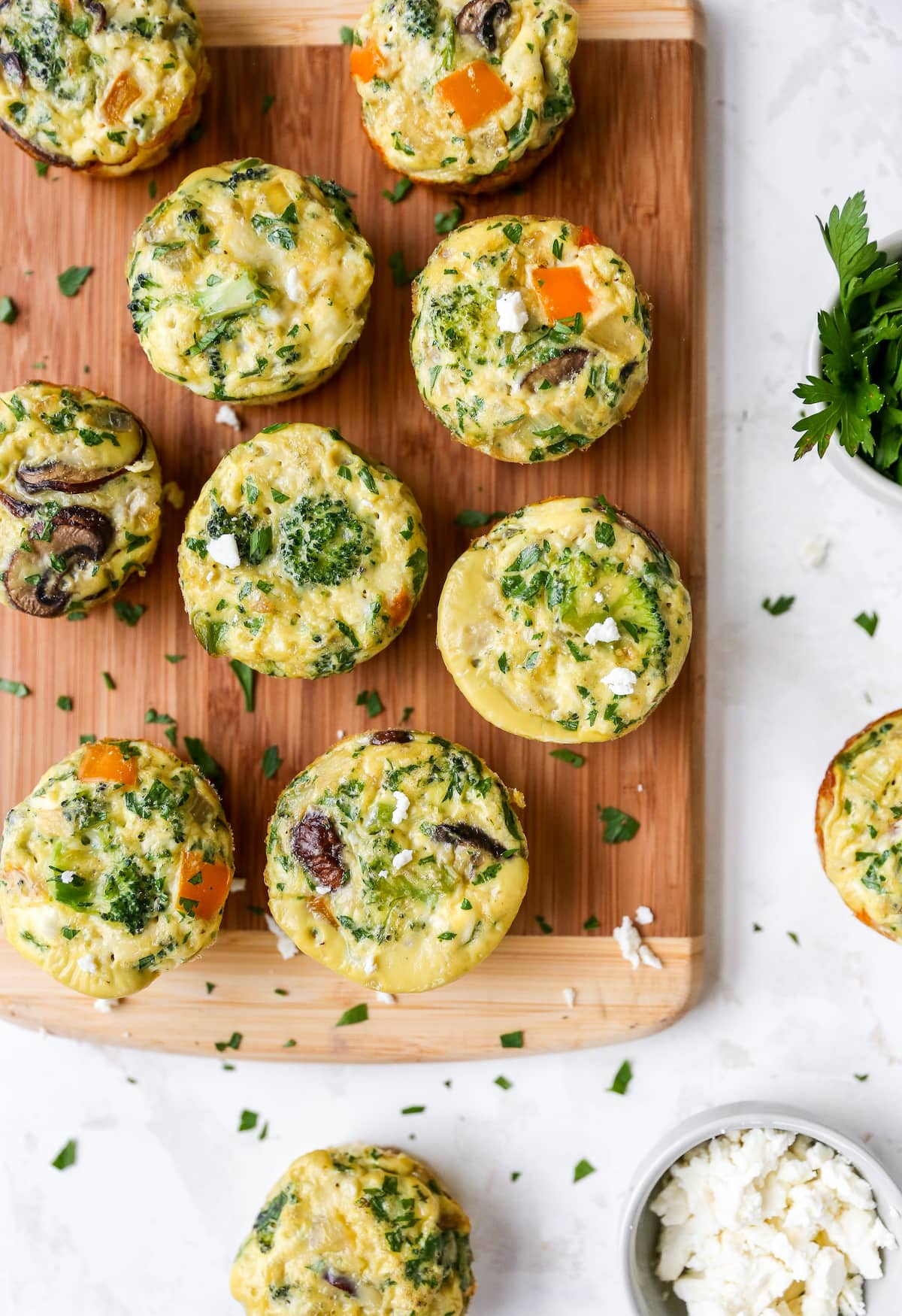 Baked egg and veggie cups on a wood cutting board.