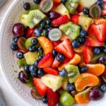 Bowl of fruit salad with strawberries, clementines, kiwi, grapes, blueberries and pineapple. Fruit salad is topped with lime zest.
