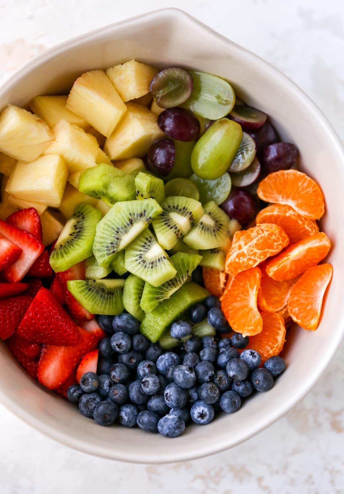 Mixing bowl with pineapple chunks, grapes, clementine segments, kiwi slices, blueberries and strawberries.