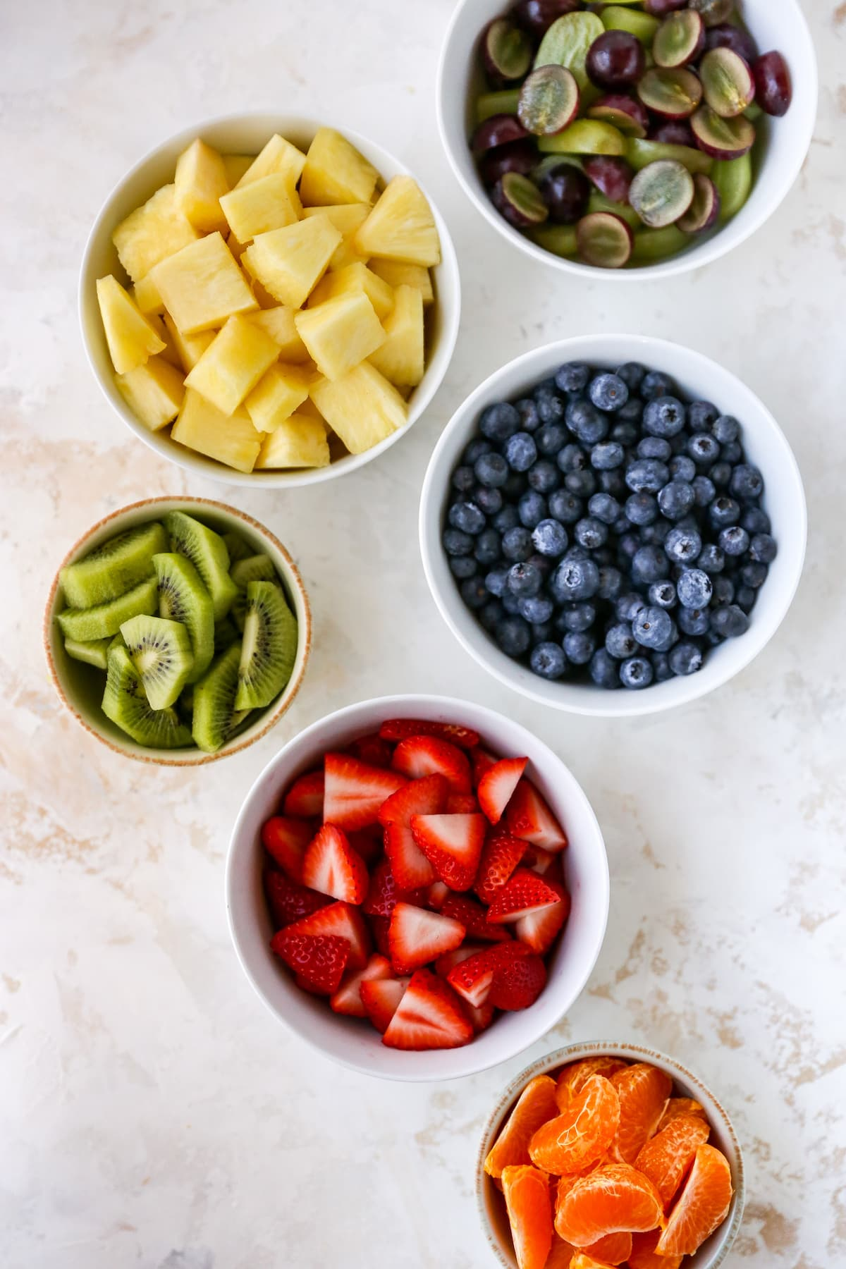 Separate bowls of grapes, pineapple, blueberries, kiwi, strawberries and clementine segments.