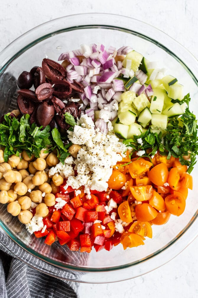 Mixing bowl with kalamata olives, red onion, cucumber, parsley, tomatoes, pepper, chickpeas and feta before being mixed together.