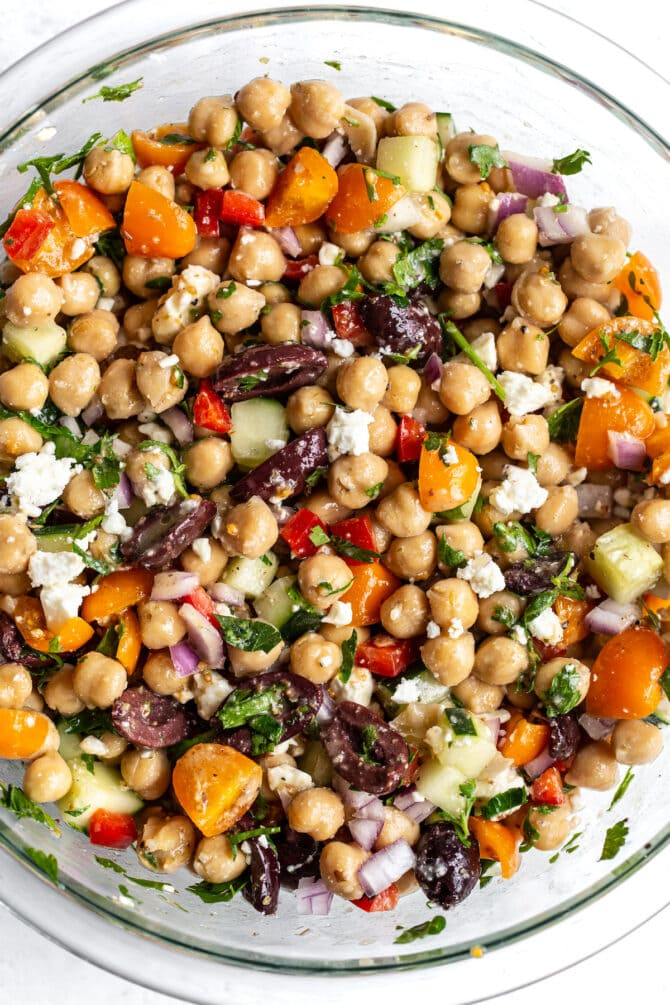 Glass mixing bowl with Greek chickpea salad: chickpeas, peppers, cucumber onion, feta, olives and herbs.