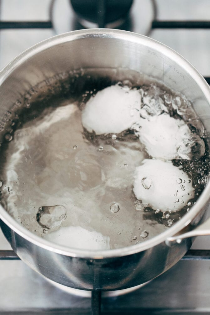 Eggs being boiled in a pot of water.