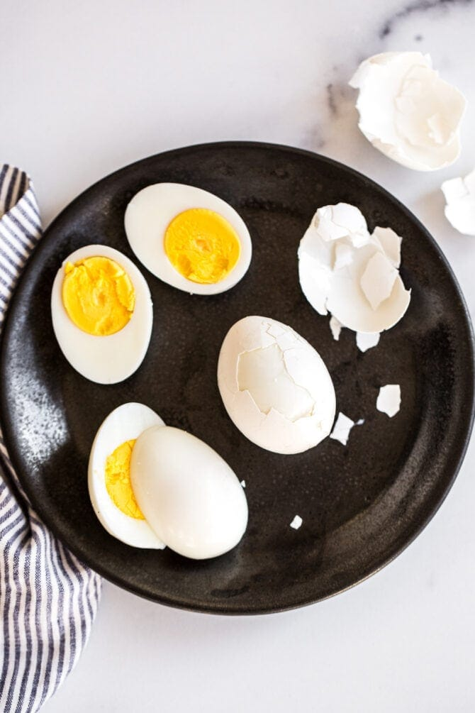 Hard boiled eggs being peeled on a plate.