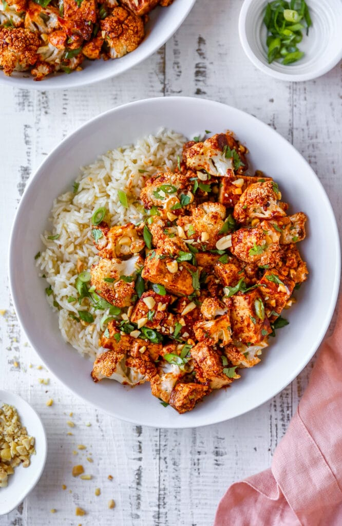 Bowl of kung pao tofu and cauliflower served with rice.