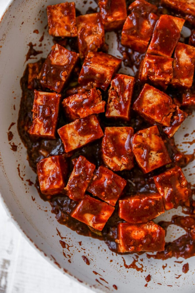 Cubes of tofu being cooked in a pan with kung pao sauce.