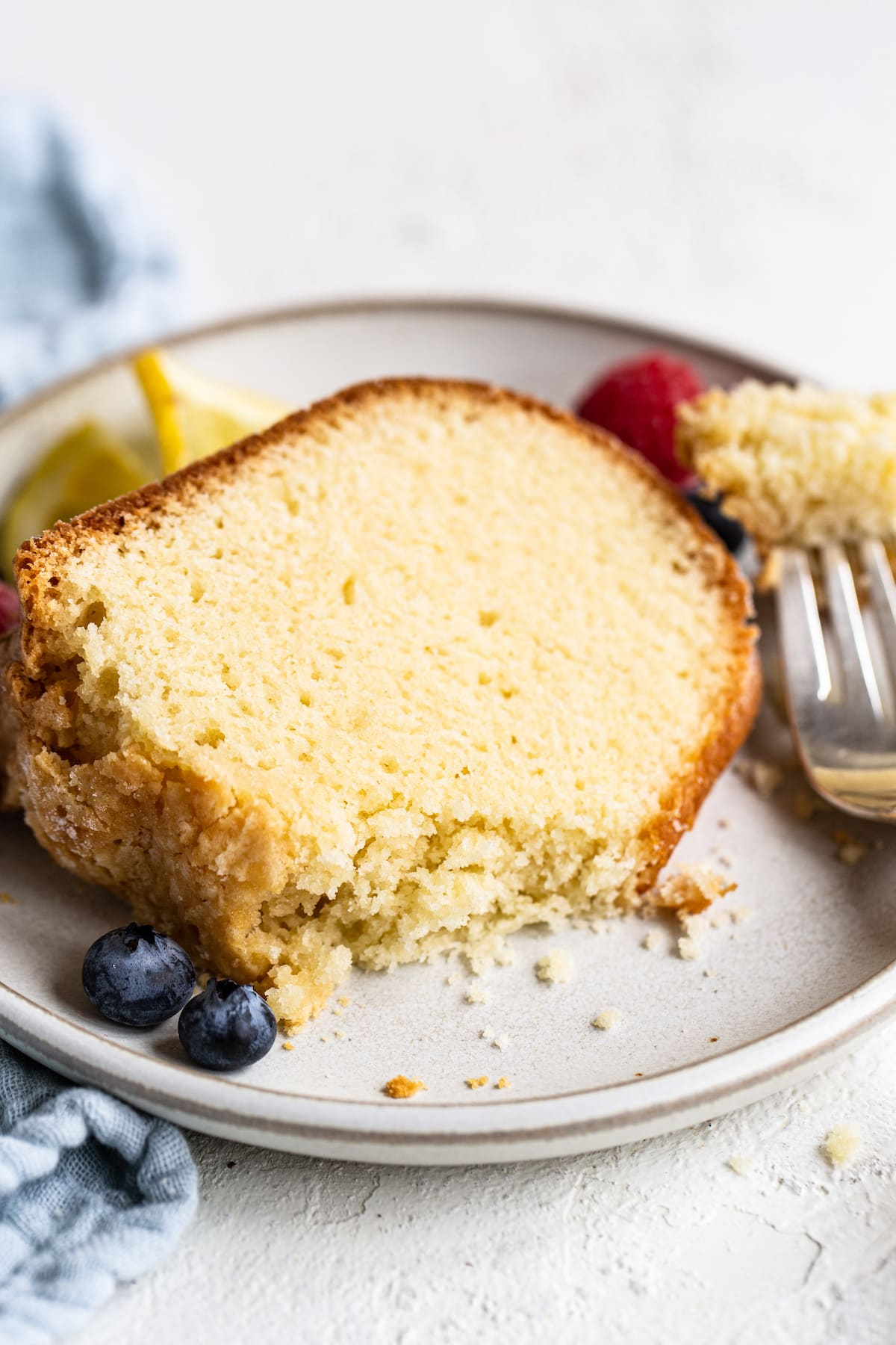 Slice of pound cake on a plate garnished with berries. Fork has taken a bite out of the cake.