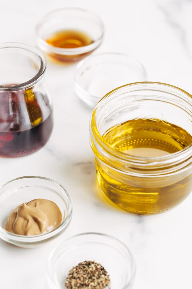 Ingredients to make red wine vinaigrette measured out in bowls and jars.