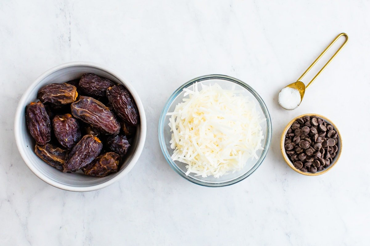 Three bowls of dates, coconut flakes and chocolate chips. Teaspoon of coconut oil.