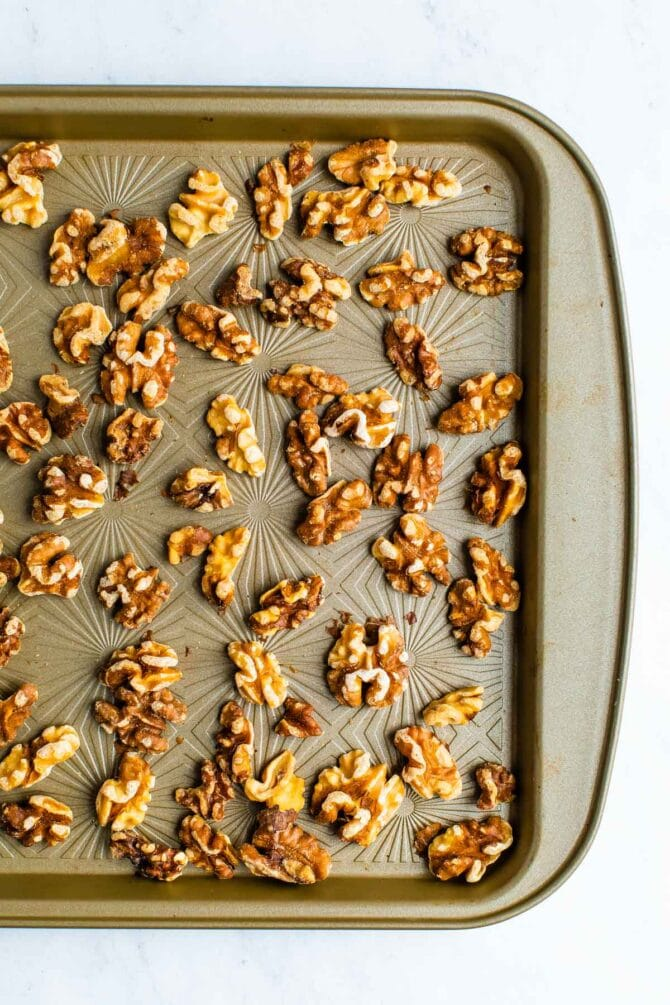 Toasted walnuts on a cookie sheet.