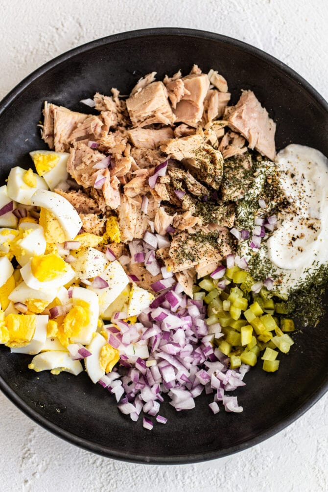 Bowl with hard boiled eggs, onion, pickles, spices, Greek yogurt and tuna.