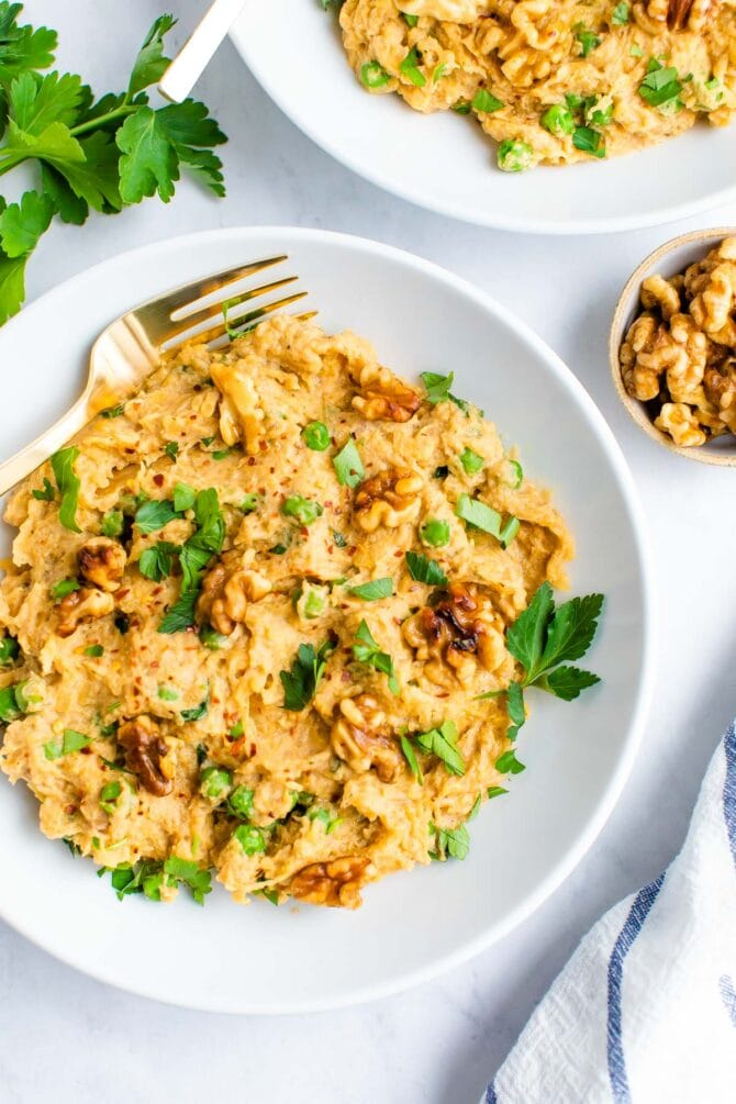Plate of spaghetti squash noodles with a creamy walnut sauce and topped with walnuts and parsley.