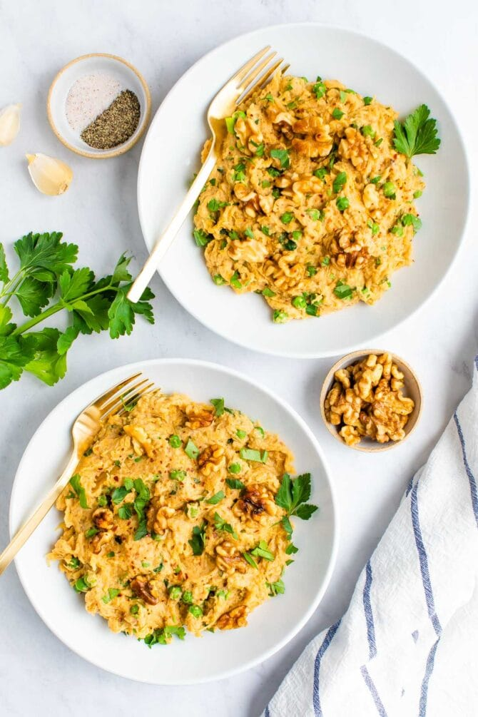 Two plates of spaghetti squash noodles with creamy walnut sauce, topped with walnuts and parsley. Parsley, a cloth napkin, garlic, a bowl of salt and pepper and a bowl of walnuts are around on the table beside the plates.