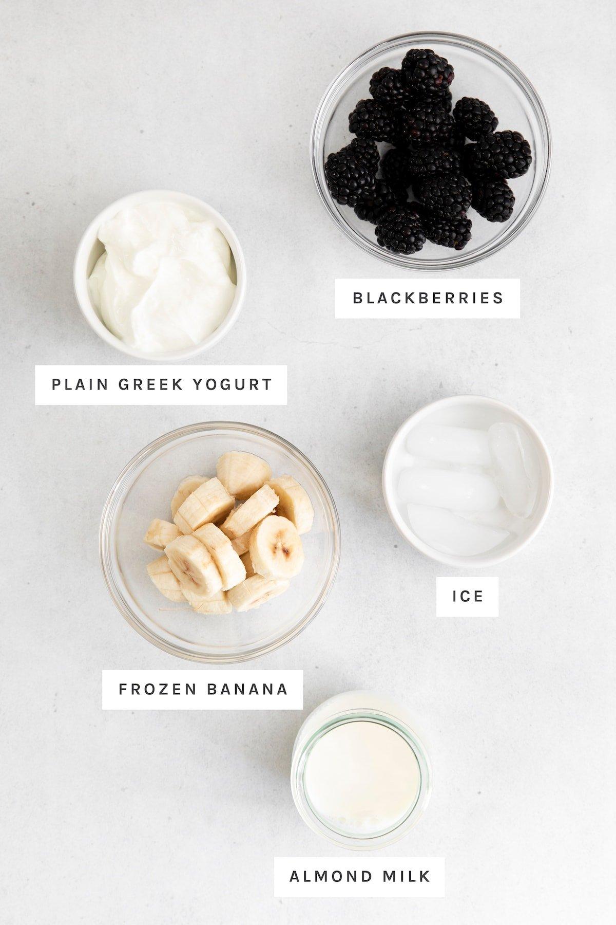 Measured out ingredients in bowls for blackberries, greek yogurt, ice, frozen banana and almond milk.