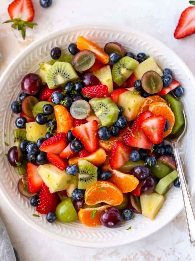 Bowl of fruit salad with strawberries, clementines, kiwi, grapes, blueberries and pineapple. Fruit salad is topped with lime zest. Bowl has a serving spoon in it. To the side of the bowl is a cloth napkin and more strawberries and blueberries.