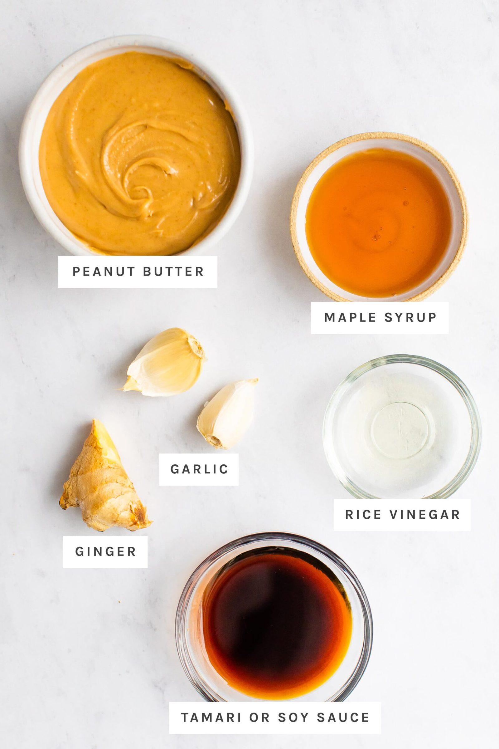 Peanut butter, maple syrup, garlic, ginger, rice vinegar and tamari measured out.