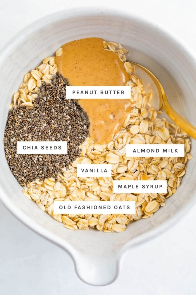 وعاء مع زبدة الفول السوداني وحليب اللوز وشراب القيقب والفانيليا والشوفان وبذور الشيا.  كل عنصر له ملصق.