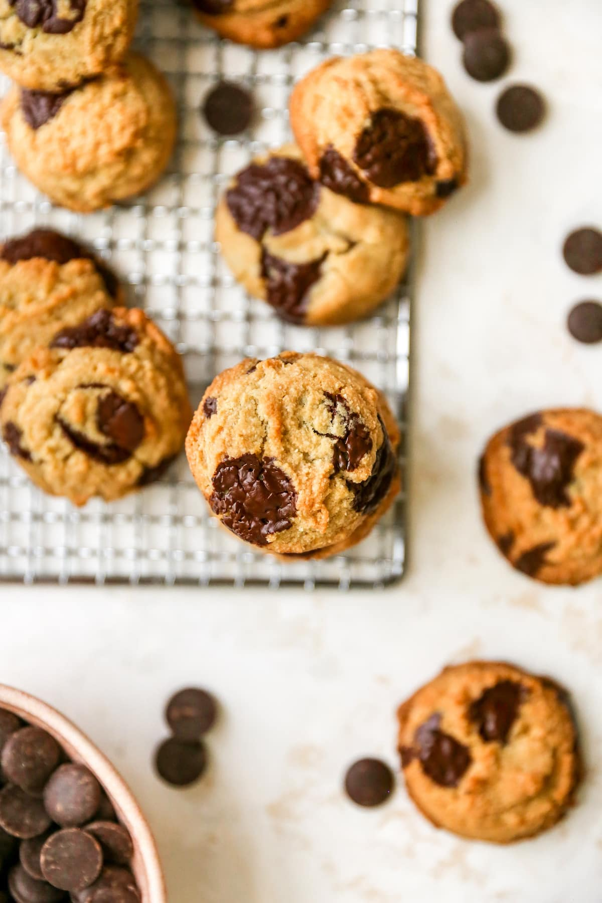 Almond flour chocolate chip cookies on a table and cooling rack surrounded by chocolate chips.