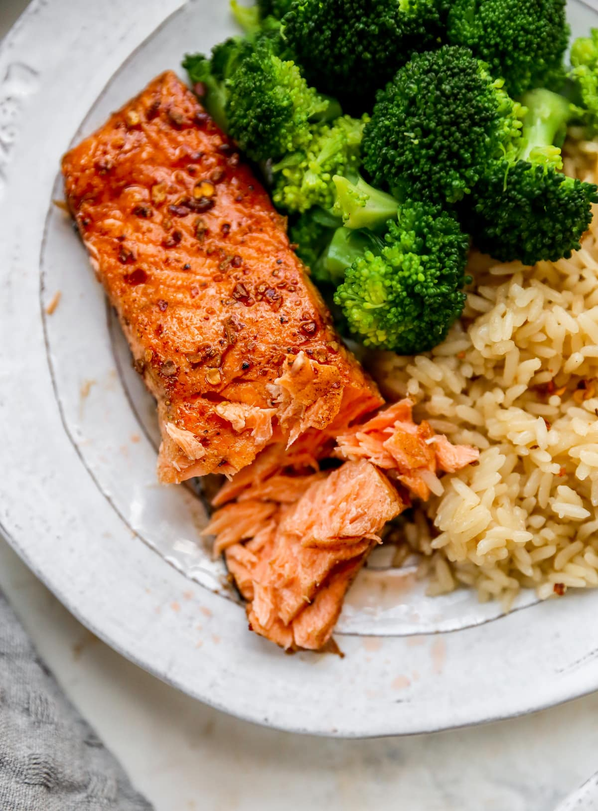 Plate with a piece of balsamic salmon, brown rice and broccoli. Salmon has a bite taken out of it.