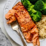 Plate with a piece of balsamic salmon, brown rice and broccoli. Fork is taking a bite from the salmon.