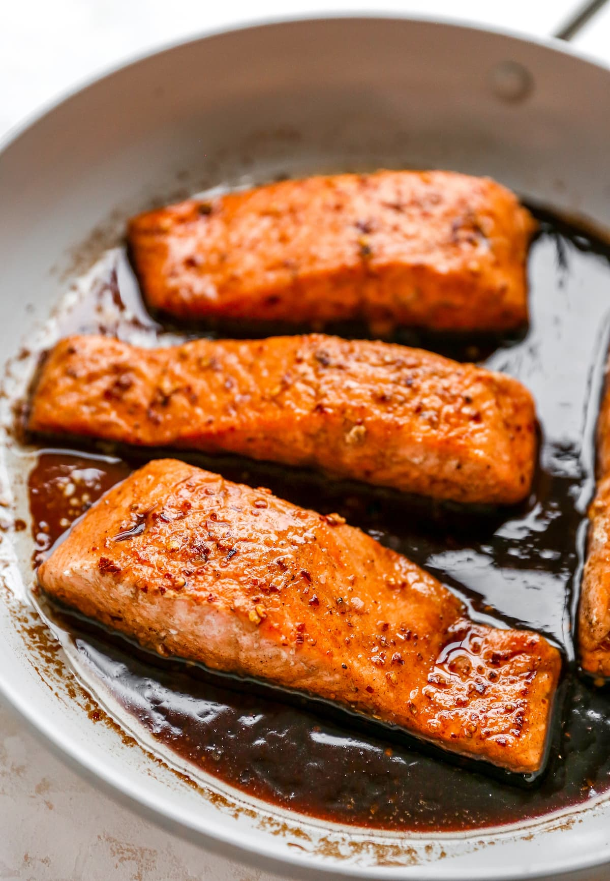 Four salmon filets in a skillet with balsamic glaze.