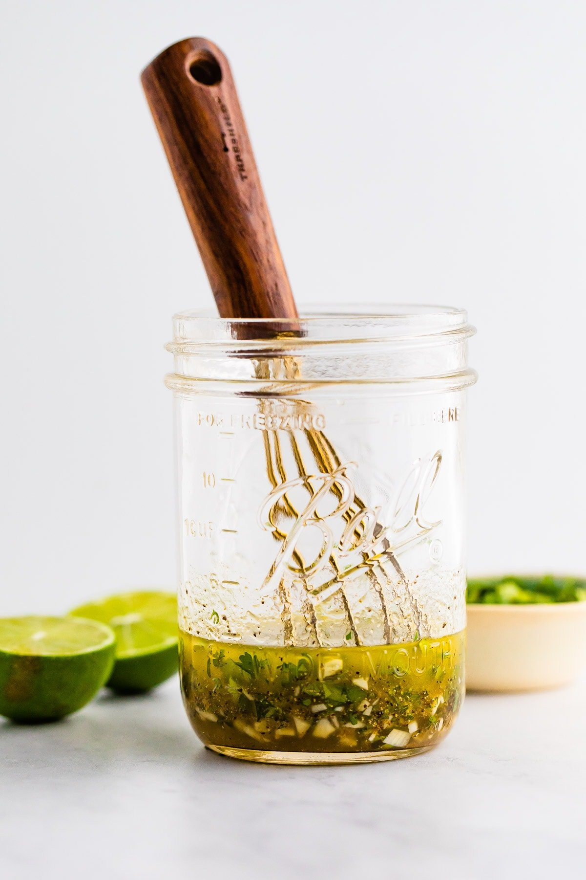 Mason jar with a whisk and ingredients for a cilantro lime dressing.