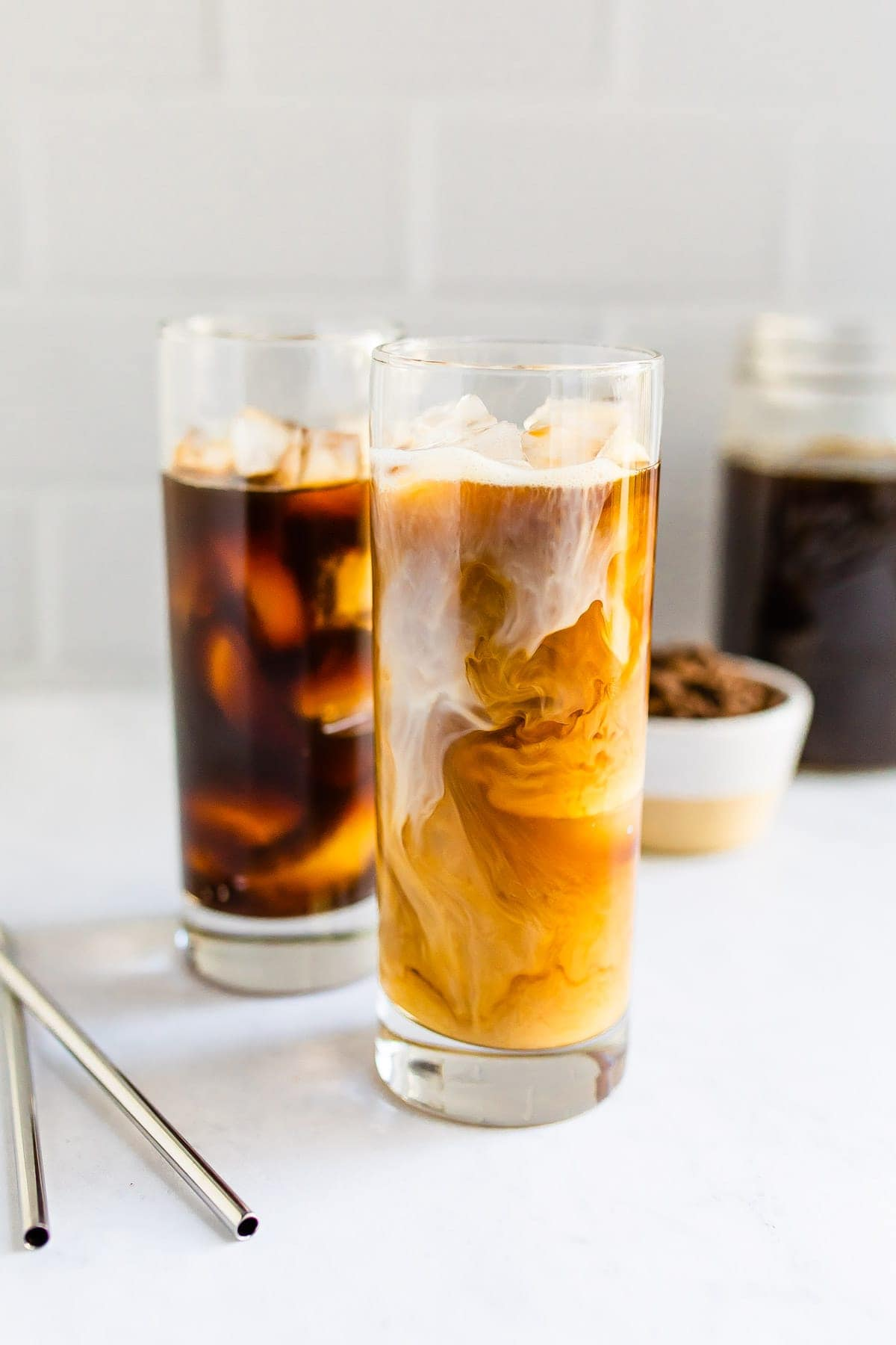 Two tall glasses of cold brew. One is black and one had cream being swirled in.