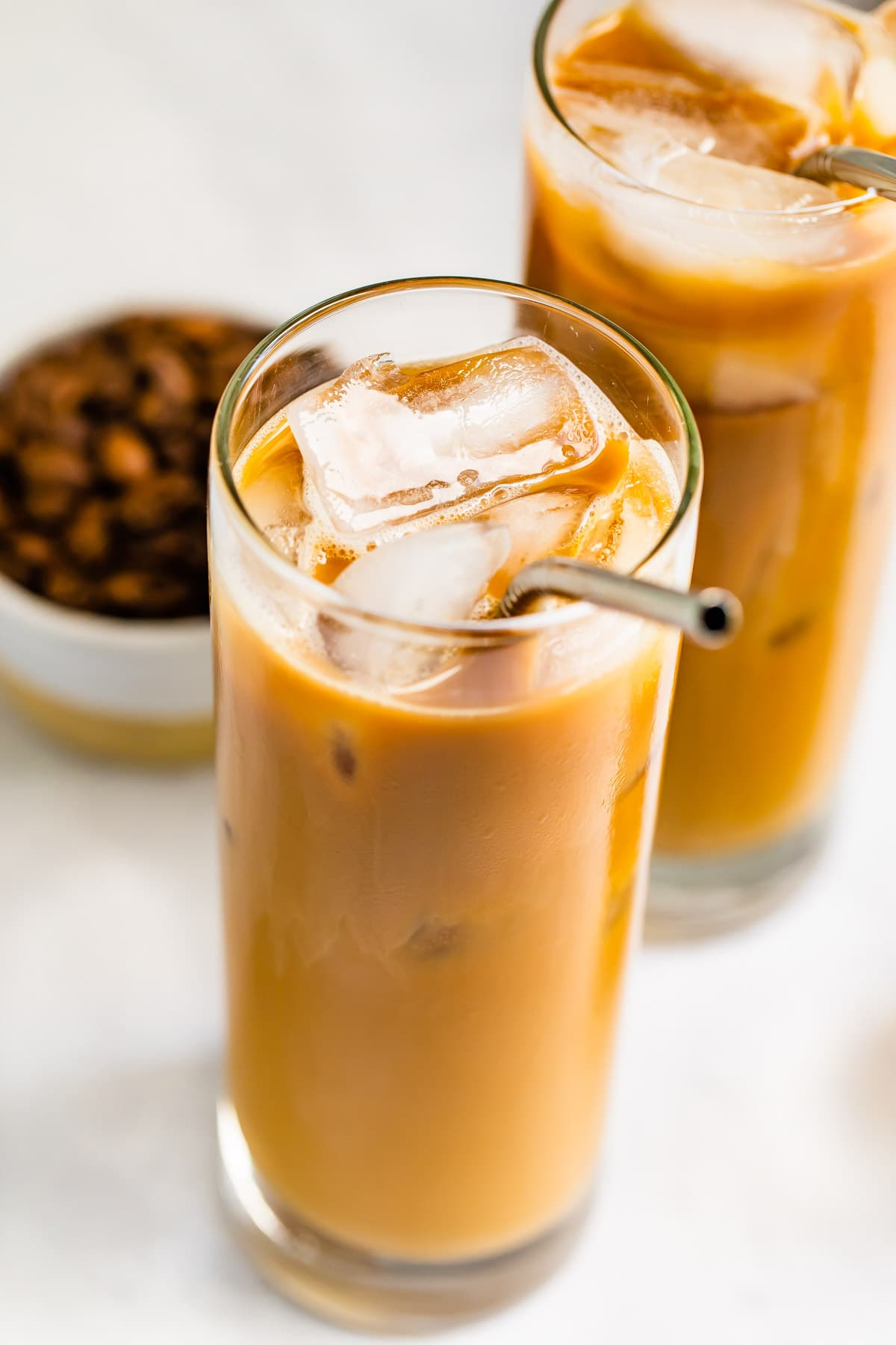 Glass of cold brew and cream with a metal straw in the glass.