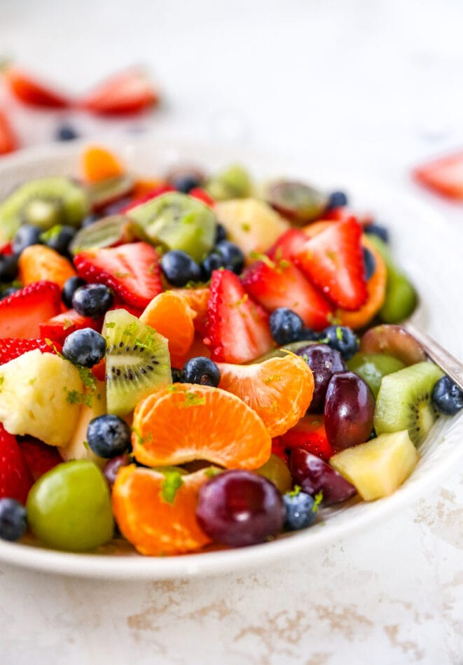 A bowl of fruit salad with clementines, kiwi, berries and grapes.