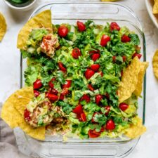 Square dish of Mexican layer dip with tortilla chips in the dip.