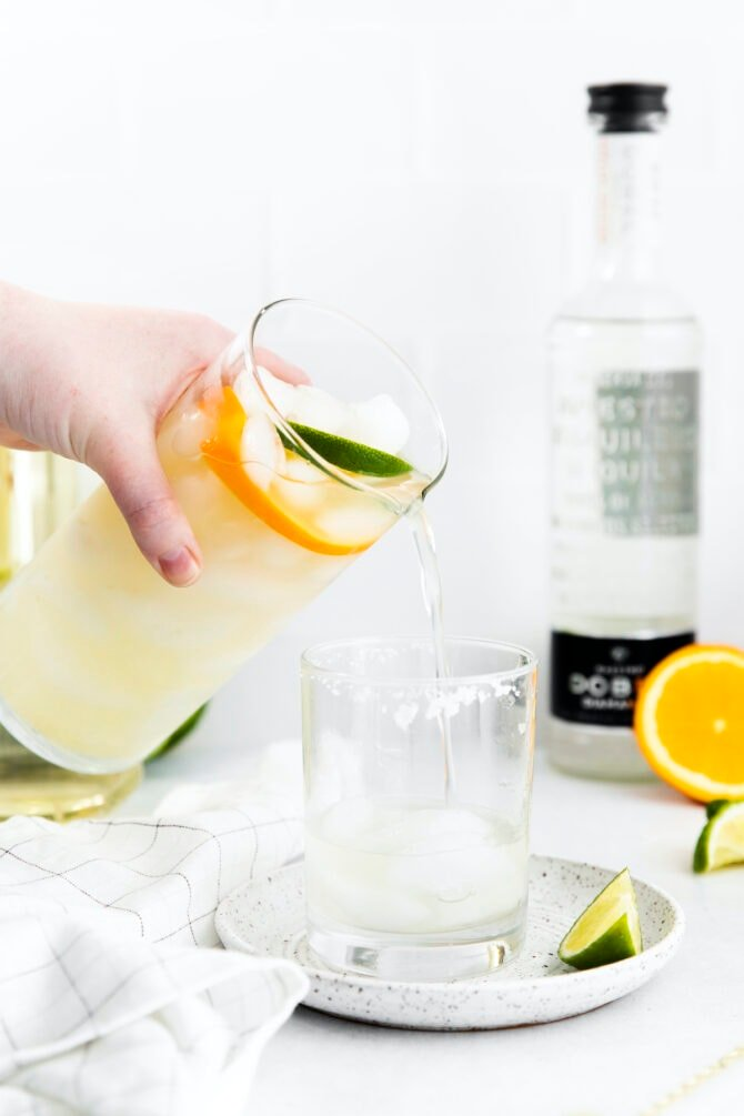 Pouring margarita mix into a glass of ice.