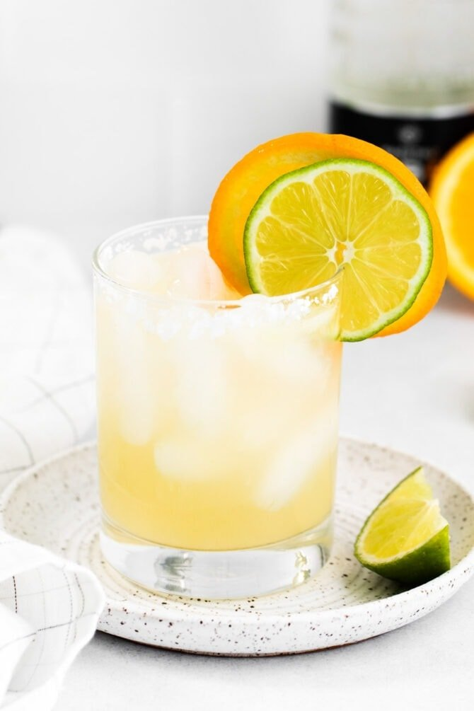 Glass of a skinny margarita with slices of lime and orange.