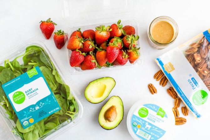 Package of baby spinach, strawberries, goat cheese, pecans, an avocado and jar of dressing on a table.