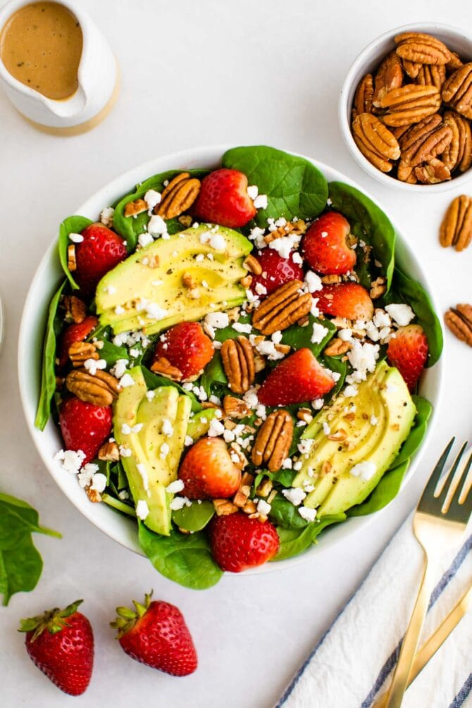 Spinach salad with avocado, strawberries, pecans, goat cheese and balsamic dressing. Forks and more ingredients are beside the bowl on the table.
