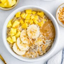 Bowl of overnight oats topped with pineapple, mango, coconut, banana and peanut butter.