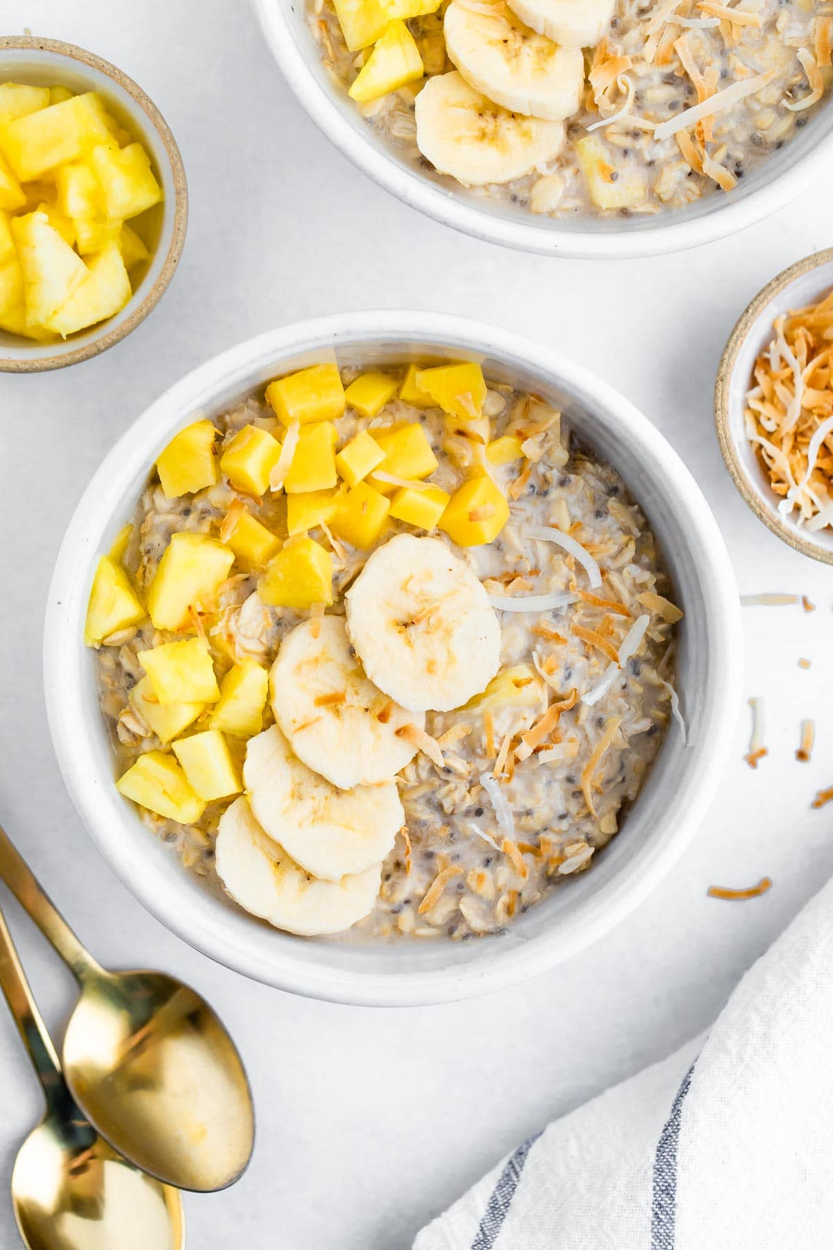 Bowl of overnight oats topped with pineapple, mango, coconut and banana