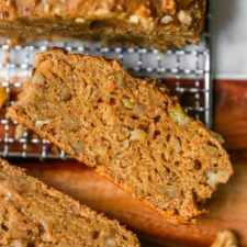 Slice of vegan banana bread on a cooling rack.
