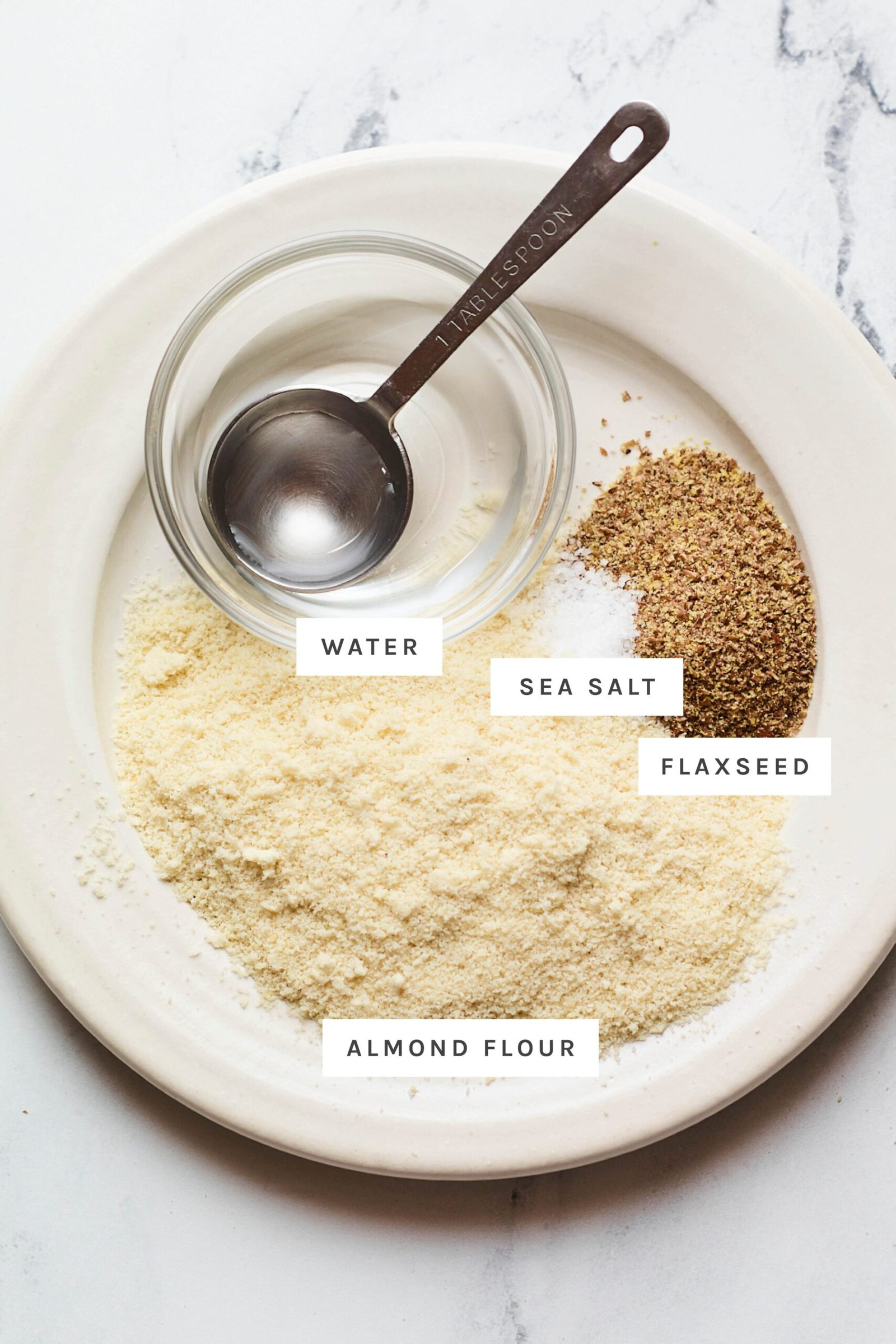 Water, flaxseed, salt and almond flour measured out on a plate.