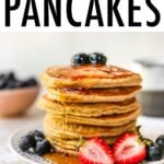 Stack of almond flour pancakes served with berries and maple syrup.