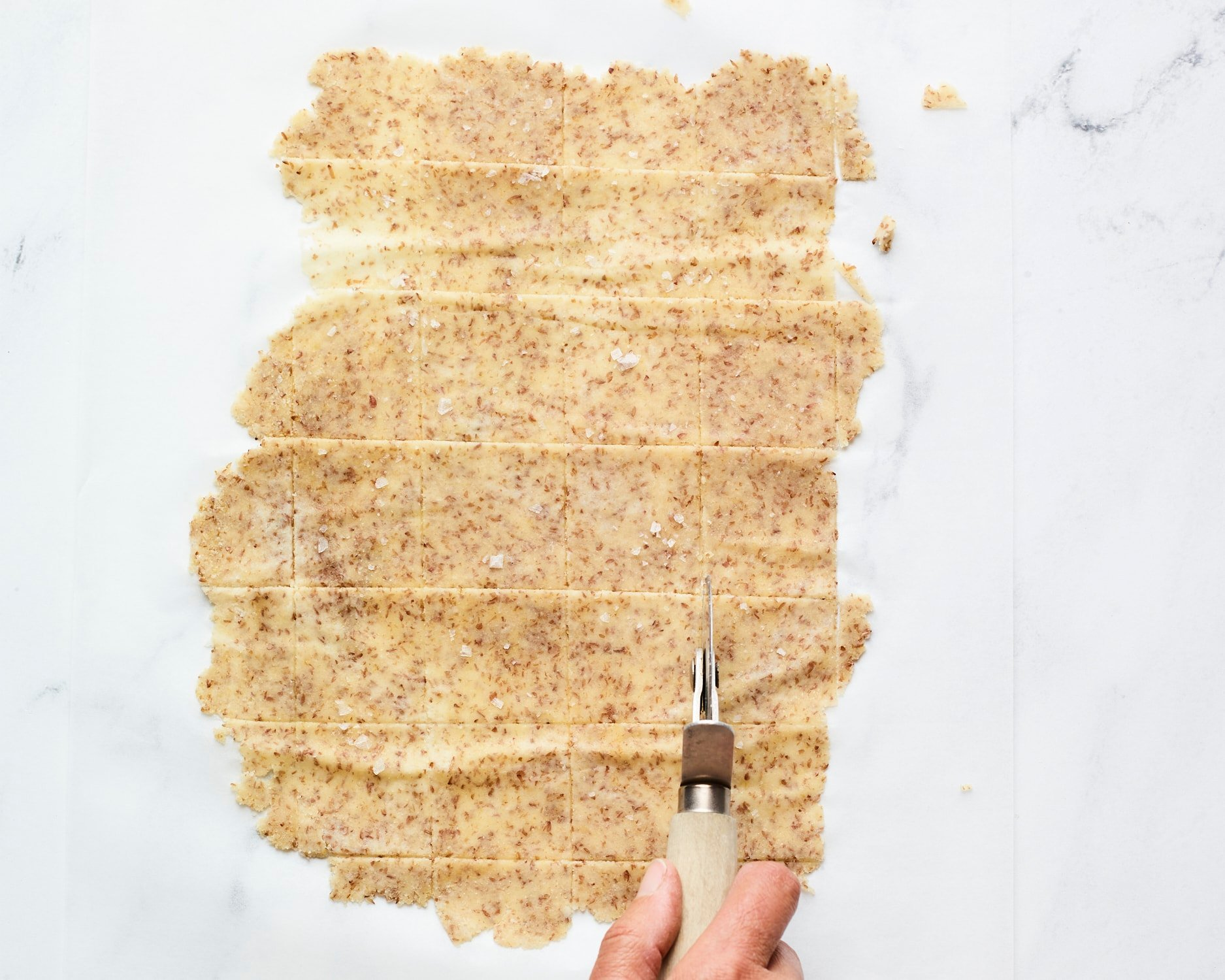 Pizza cutter slicing dough into squares for almond flour crackers.