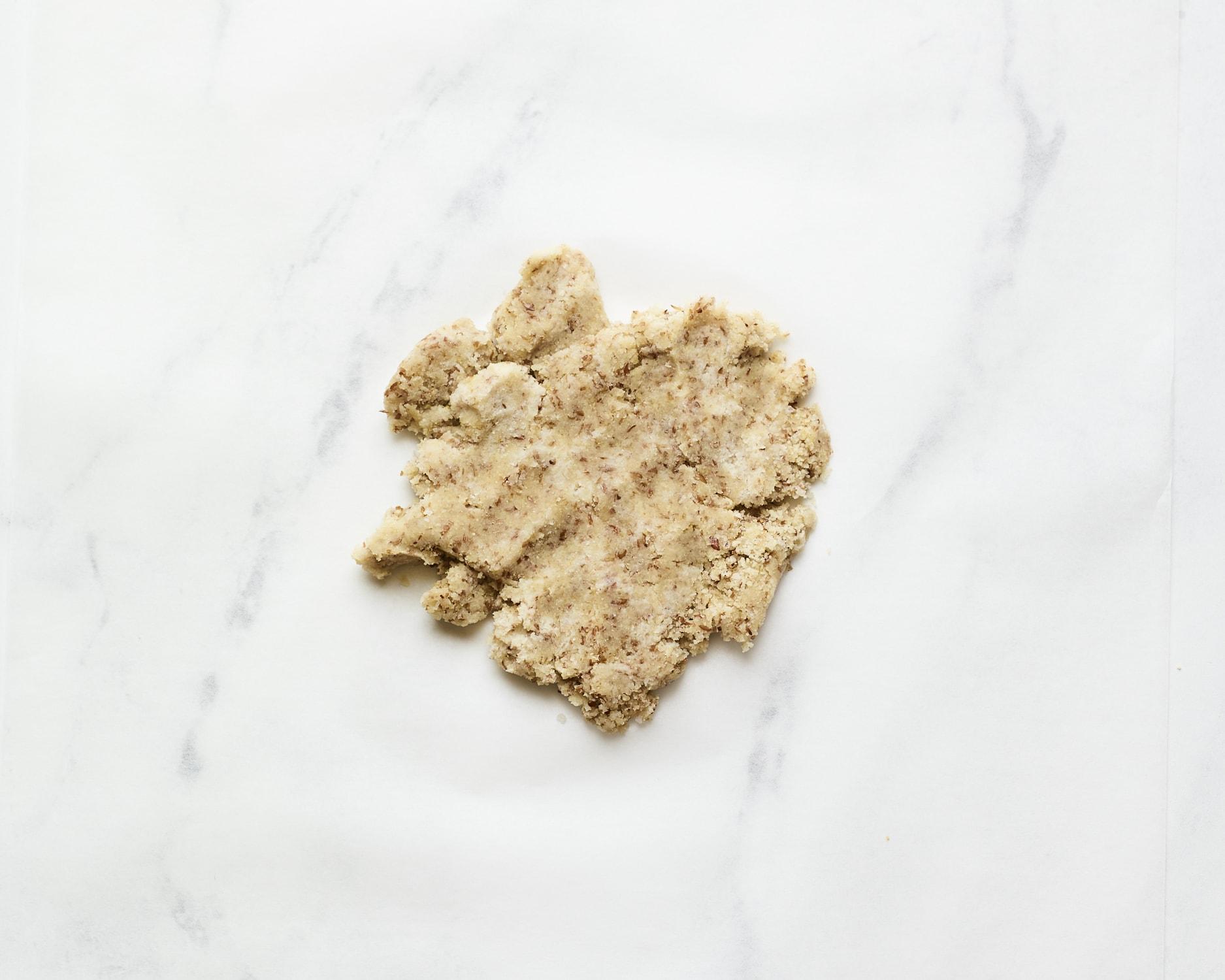 Almond flour cracker dough on a marble slab.