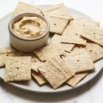 Almond flour crackers on a plate with hummus.