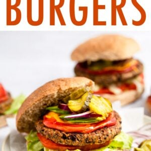 Black bean burger on a bun with lettuce, tomato, onion, ketchup, mustard and pickles.